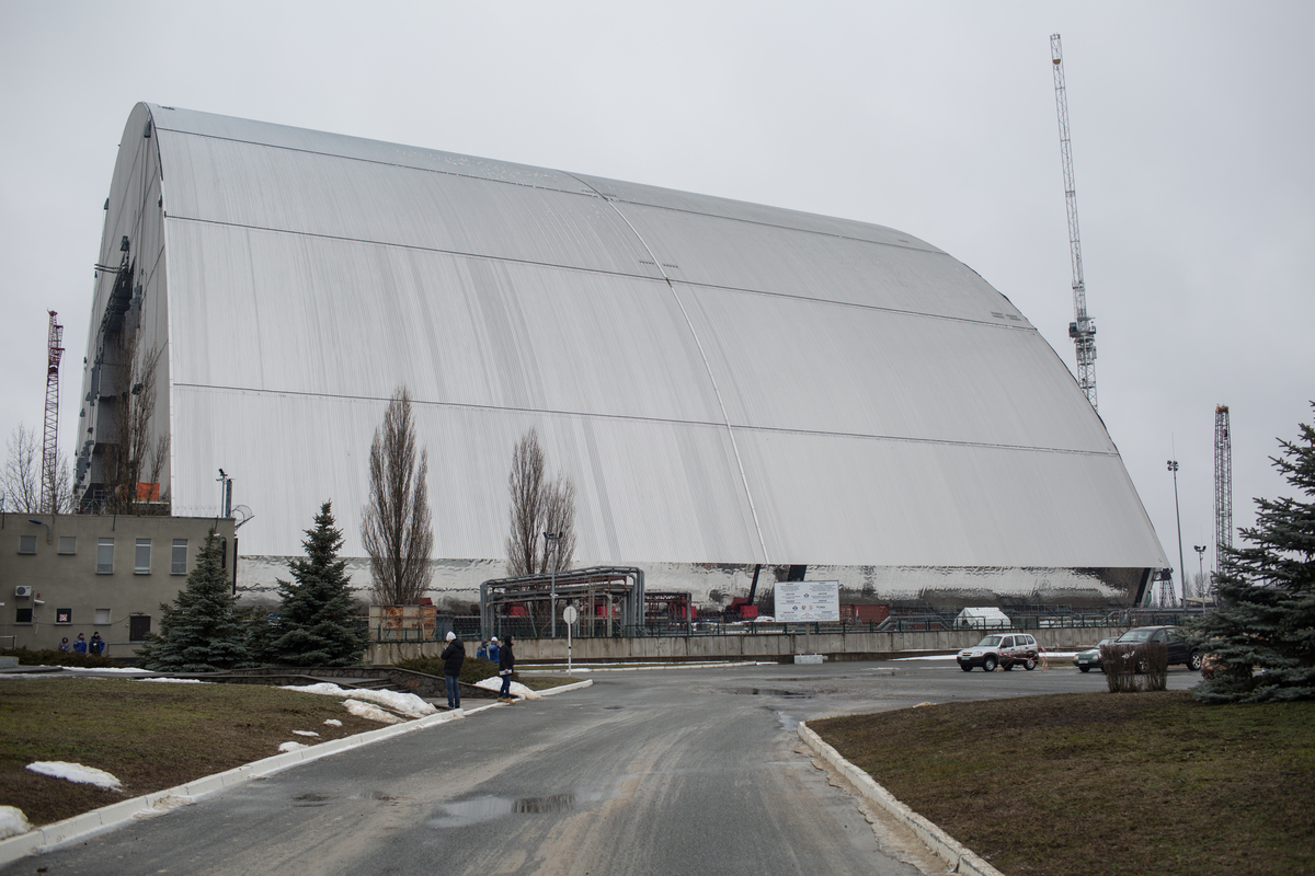 ... 30 anos após o acidente de Chernobyl, uma nova cobertura foi construída para substituir o sarcófago construído na época. A estrutura irá conter a contaminação por cerca de 100 anos, tempo ínfimo para que a radiação caia para níveis seguros, mas deve servir para que novas tecnologias sejam desenvolvidas para lidar com o reator derretido. © Denis Sinyakov / Greenpeace