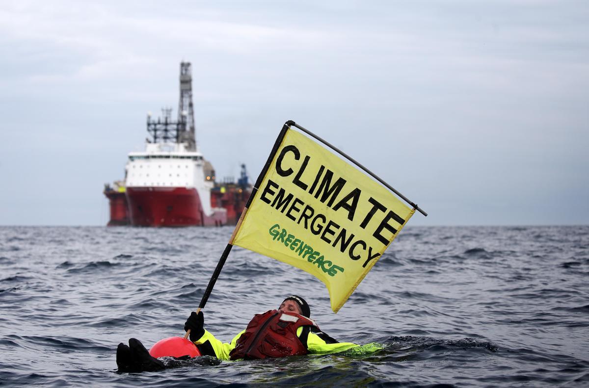 """Ativista Sarah North nas águas frias do Mar do Norte com o cartaz """"Emergência Climática"""". © Greenpeace"""