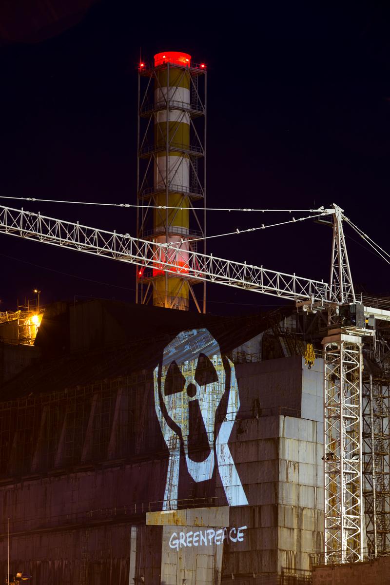 """Protesto do Greenpeace marcando os 30 anos do desastre nuclear de Chernobyl. A projeção no sarcófago que envolve o reator derretido mostrou imagens de sobreviventes (fotos de Robert Knoth) e mensagens como """"Chernobyl 30 anos: nunca mais"""", """"Chernobyl: sofrimento sem fim"""" e """"Chega de energia nuclear"""" em vários idiomas. © Daniel Müller / Greenpeace"""