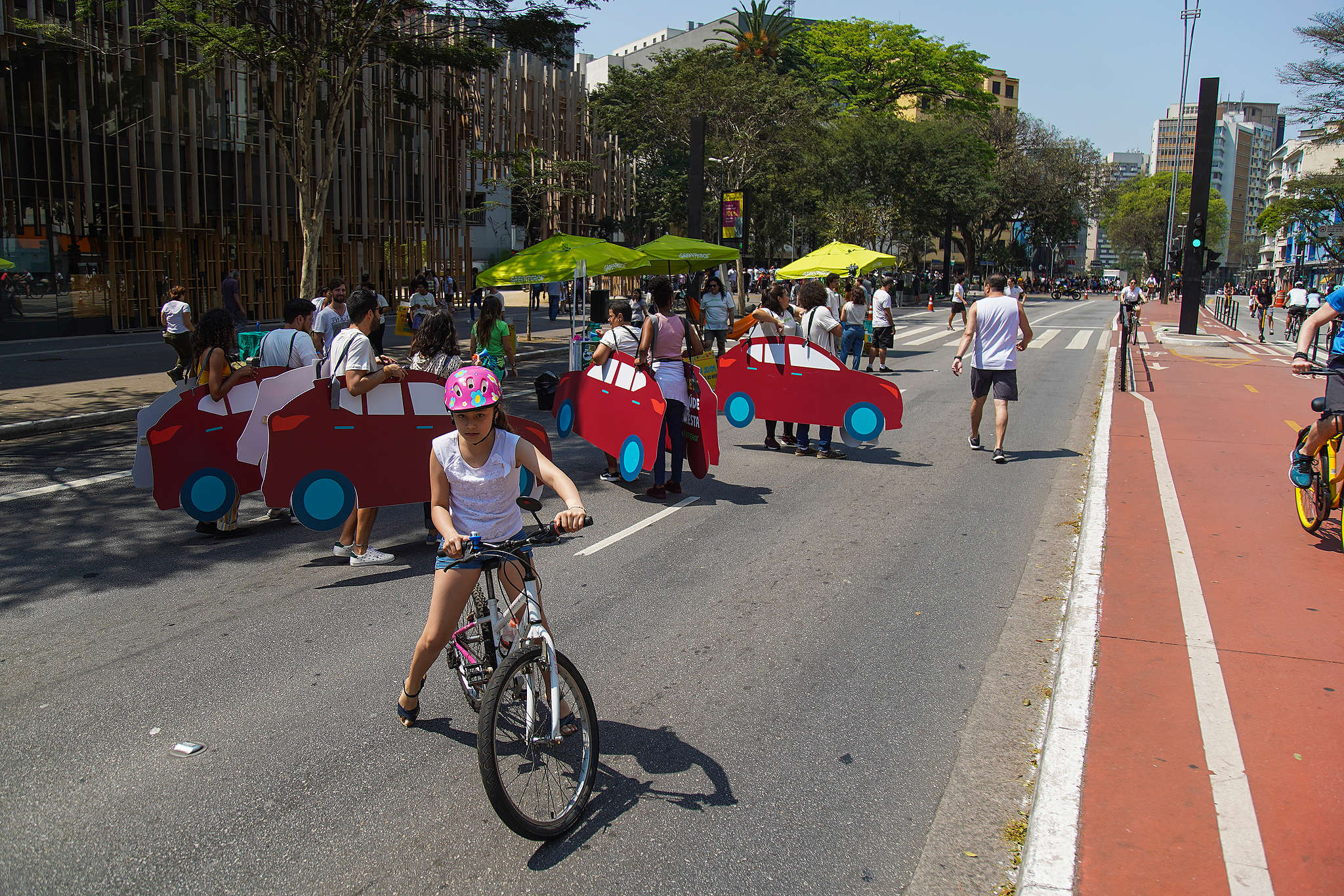 """No primeiro plano, pessoas vestidas de carros promovem um pequeno """"congestionamento"""" e impedem a passagem de pedestres pela Avenida Paulista; com perspectiva da avenida em dia de sol"""