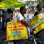 """Garota de tranças segura placa com os dizeres """"Pela sua saúde e a da cidade, vem pra marcha!""""; ao fundo, homem de óculos segura placa com os dizeres """"dia 20/09, às 16 horas no Masp""""; ambos estão de bicicleta na Avenida Paulista; ao fundo, guarda-sol do Greenpeace"""