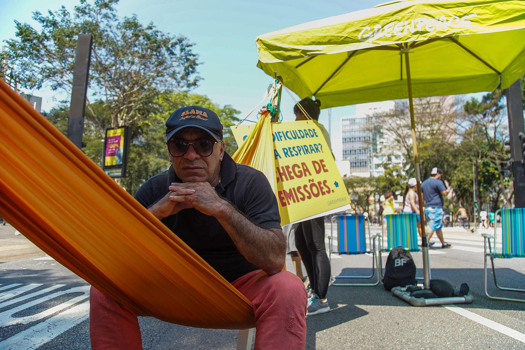 Homem de meia idade sentado na rede no meio da Avenida Paulista. Ao fundo, guarda-sol do Greenpeace e cartaz contra as emissões de gases poluentes