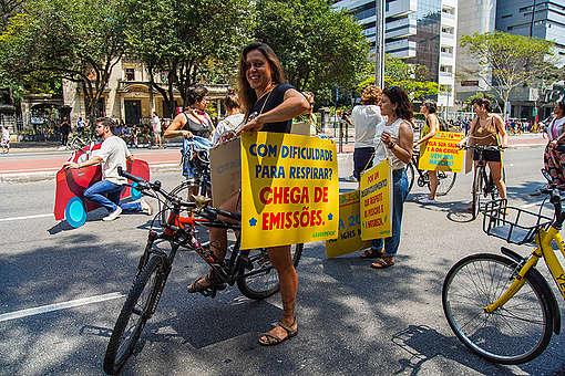 """Cicloativista segura placa com os dizeres """"Com dificuldade para respirar? Chega de emissões"""", na Avenida Paulista"""