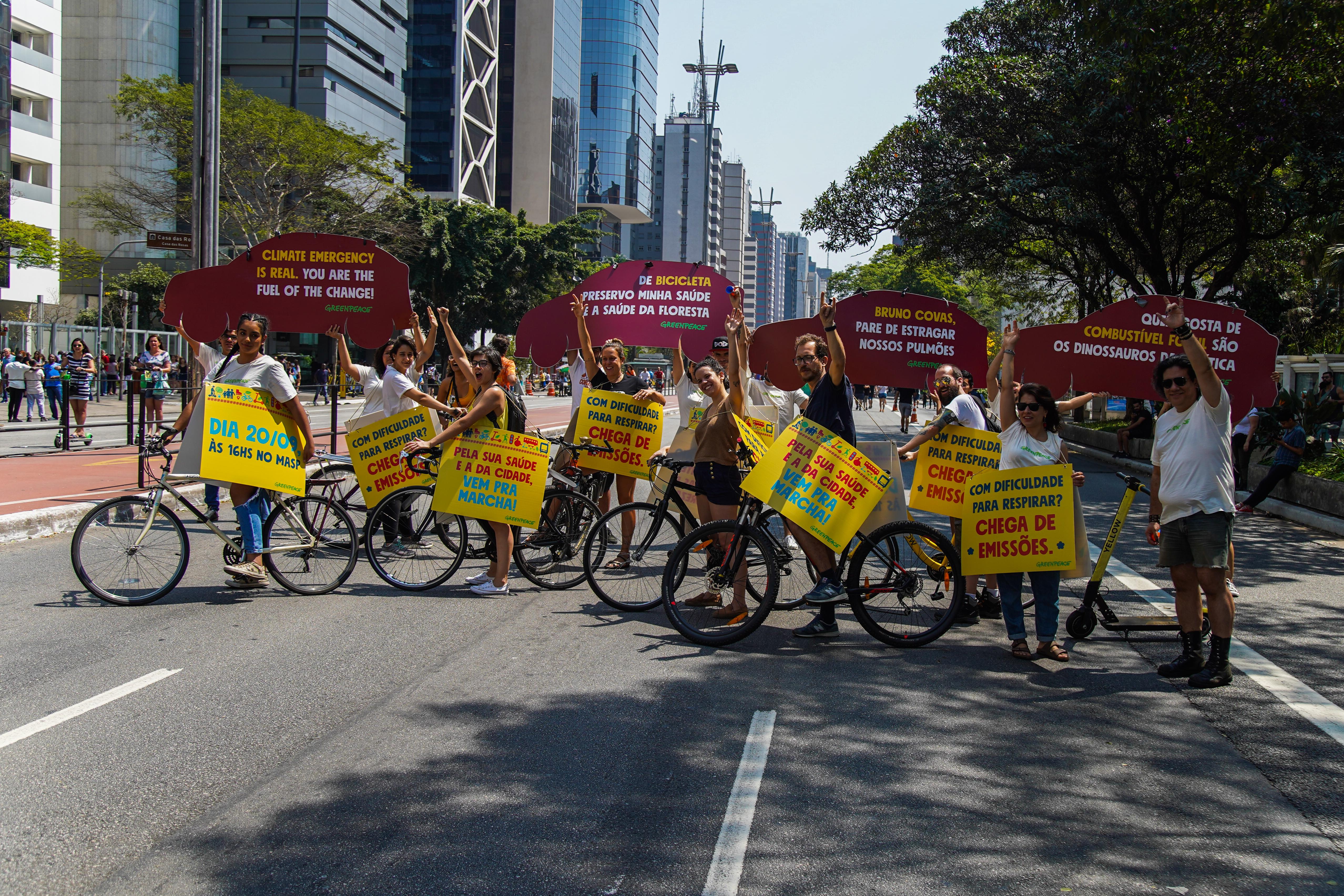 """Ativistas do Greenpeace levantam placas com os dizeres """"De bicicleta preservo minha saúde e a saúde da floresta"""", """"Bruno Covas, pare de estragar nossos pulmões"""", Quem gosta de combustível fóssil são os dinossauros da política"""", com Avenida Paulista em perspectiva, dia de sol"""