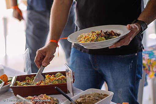 homem segura um prato de comida vegano.