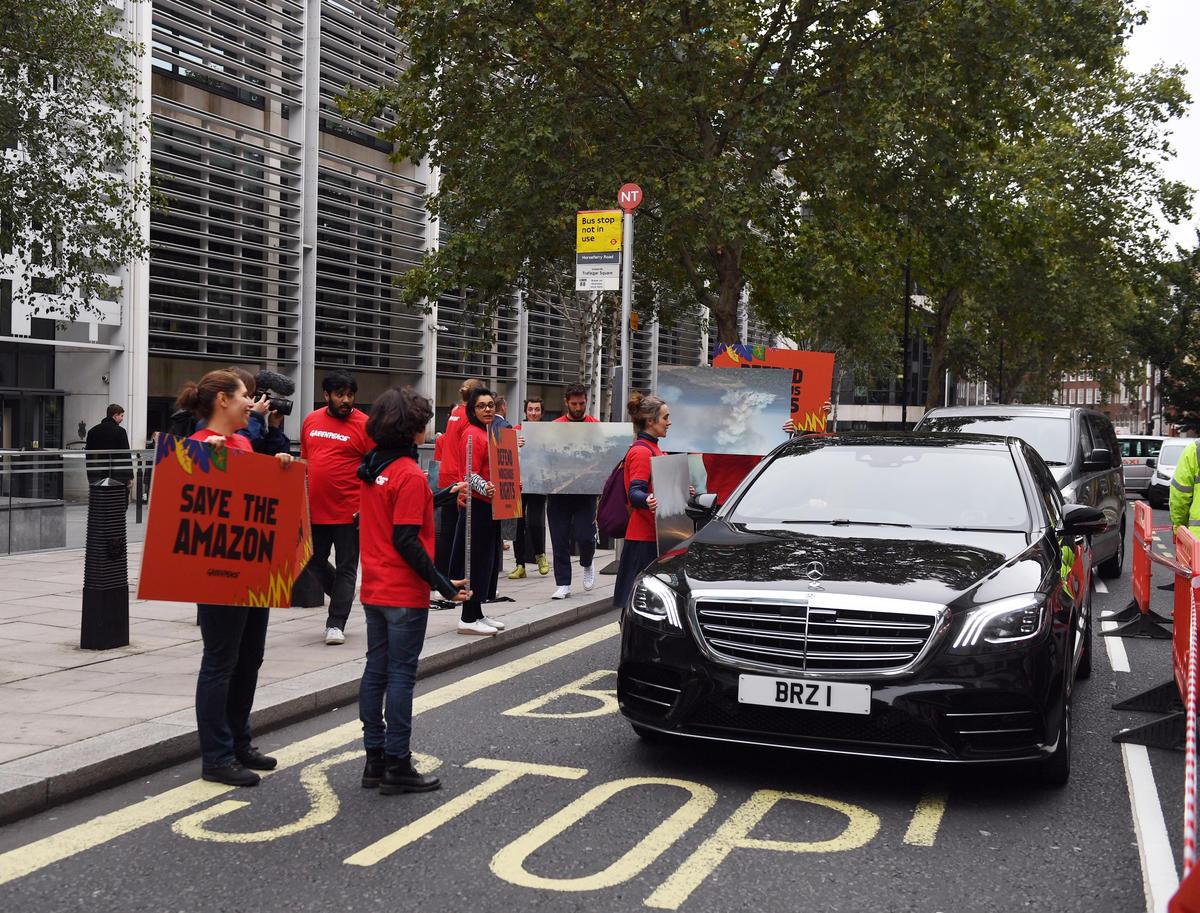 Carro oficial do Brasil chega ao prédio do escritório da ministra do meio ambiente do Reino Unido, em Londres, enquanto ativistas do Greenpeace exibem cartazes em protesto a favor da Amazônia