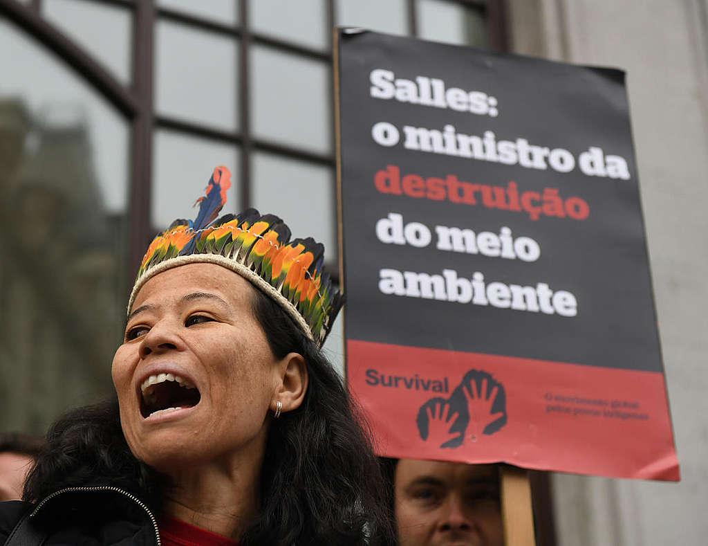 """Ativistas protestam em frente à Embaixada do Brasil em Londres, close em mulher usando um cocar e placa ao fundo com a frase """"Salles: o ministro da destruição do meio ambiente"""""""
