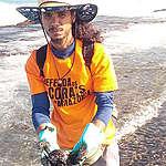 garoto fazendo limpeza de petróleo na praia
