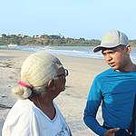 voluntário conversa com senhora idosa na praia