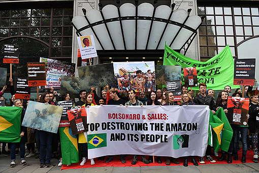 Ativistas protestam com faixas, cartazes e bandeiras do Brasil em frente á porta de entrada da Embaixada do Brasil em Londres