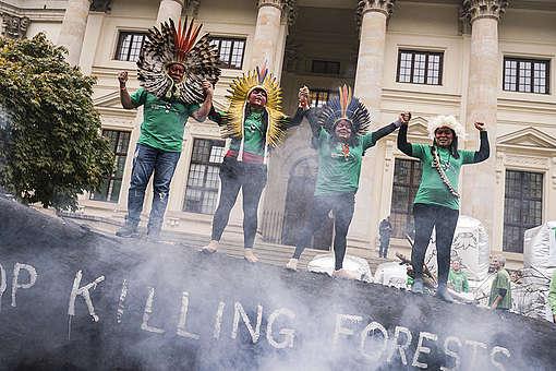 Quatro indígenas da comitiva da Jornada Sangue Indígena sobem em tronco queimado e dão as mãos em protesto em Berlim