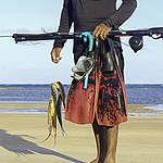 homem segura equipamentos de pesca com manchas de petróleo