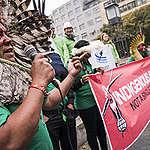 De cocar de penas preto e brancas e pintura vermelha no rosto, Kretã Kaingang discursa na frente da reunião de cúpula das indústrias de alimentos ultraprocessados, em Berlim