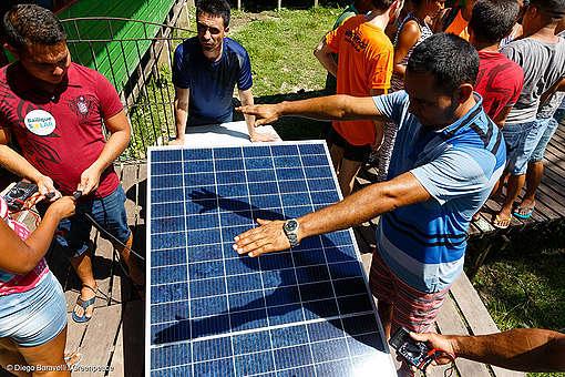 Foto mostra moradores ao lado de placa solar recebendo capacitação sobre energia solar