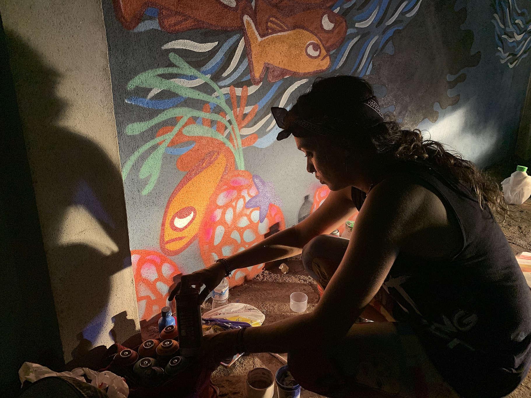 Intervenção da artista Moara pintando um mural com ilustrações de seres marinhos.
