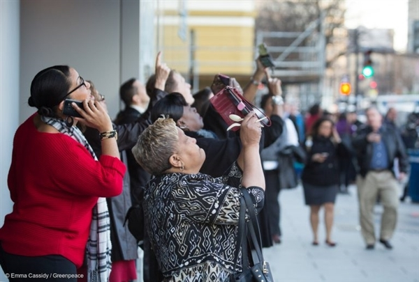 """Офис служители правят снимки и разговарят по телефона, докато гледат как активистите на """"Грийнпийс"""" разпъват банер с надпис """"Съпротива"""" на строителен кран край Белия дом на петия ден от встъпването в длъжност на Доналд Тръмп като президент на САЩ."""