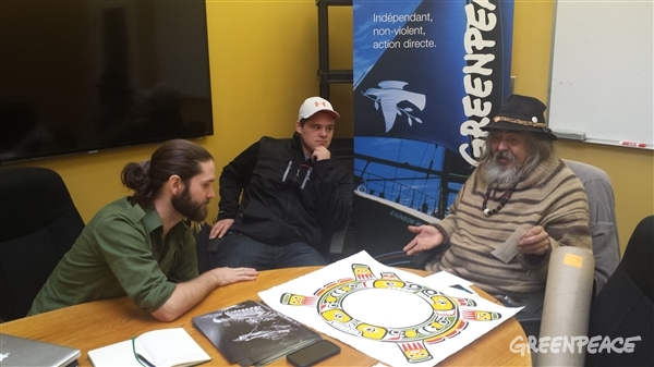 Kwakwaka'wakw artist Beau Dick revealing his new Sisiutl symbol at the Greenpeace Vancouver office (to his left is Cole Speck who applied the colours and Mark Worthing who was the researcher the project) Photo: Eduardo Sousa