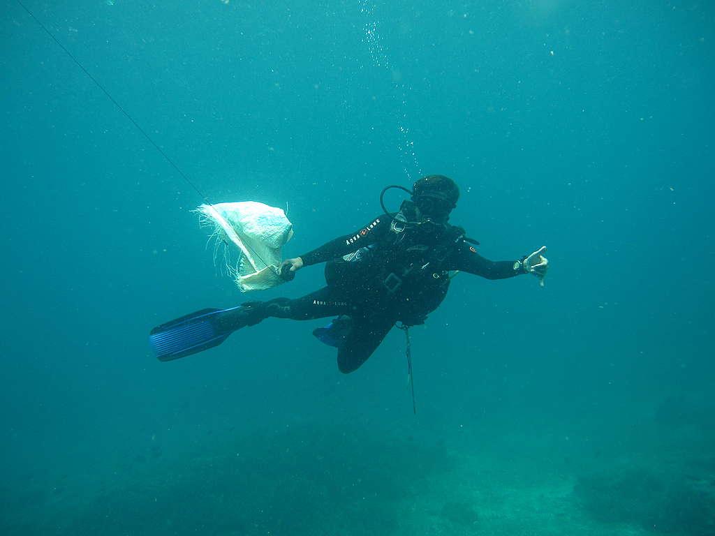 Cueillette de déchets de plastique pendant une plongée.