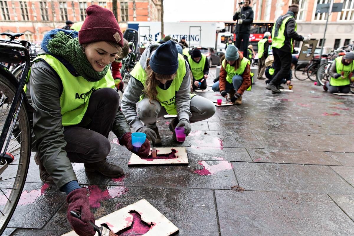 Kreativ aktion: Greenpeace forsøger at tegne tusind døde pattegrise foran Miljø- og Fødevareministeriet. © Andreas Bro