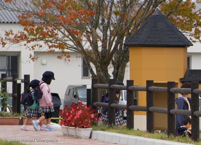 Children leaving new kindergarten in Iitate, Fukushima prefecture. Iitate, which lies 30-45km northwest of the Fukushima Daiichi nuclear plant, was heavily contaminated by radioactive fallout in 2011. The Japanese government lifted the evacuation order for most of Iitate in March 2017. Greenpeace radiation surveys in the this area from 2015 and up to October 2018, show levels of radiation, particularly in the forested areas, remain high and above international safety maximum limits. This is despite a massive decontamination program by the Japanese government. Seventy percent of Iitate is mountainous forest which cannot be decontaminated. United Nations human rights experts, and the Committee on the Rights have the child have called for the government to comply with their obligations to protect children, including from harmful radiation. This includes setting a maximum limit for public exposure, including children, to 1 miliSievert per year (1mSv/y), not the current 20mSv/y - twenty times the recommended maximum set by the International Commission for Radiation Protection. Shaun Burnie/Greenpeace.