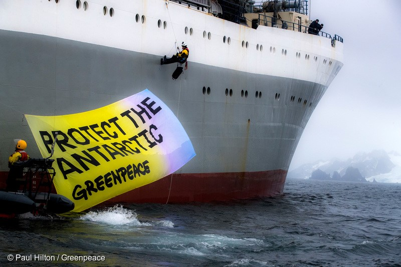 """Greenpeace activists in peaceful protest, displaying a banner saying """"Protect the Antarctic"""" on the Ukrainian krill trawler 'More Sodruzhestva' in the Bransfield Strait near Greenwich Island, Antarctic, 22nd Marech 2018. Greenpeace is calling for the krill industry to commit to stop fishing in any area being considered by governments for ocean sanctuary status, and to back proposals for marine protection in the Antarctic. Photo: Paul Hilton / Greenpeace"""