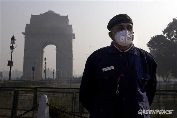 Delhi cop covered in mask stands against a hazy India Gate background