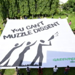 Greenpeace activists and staff unfurl a banner on World Environment Day