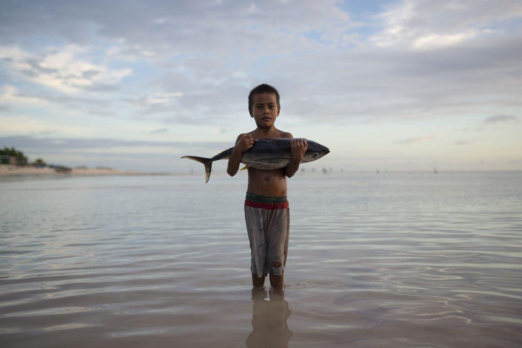 Boy with Tuna Fish Stands in Sea © Christian Åslund / Greenpeace
