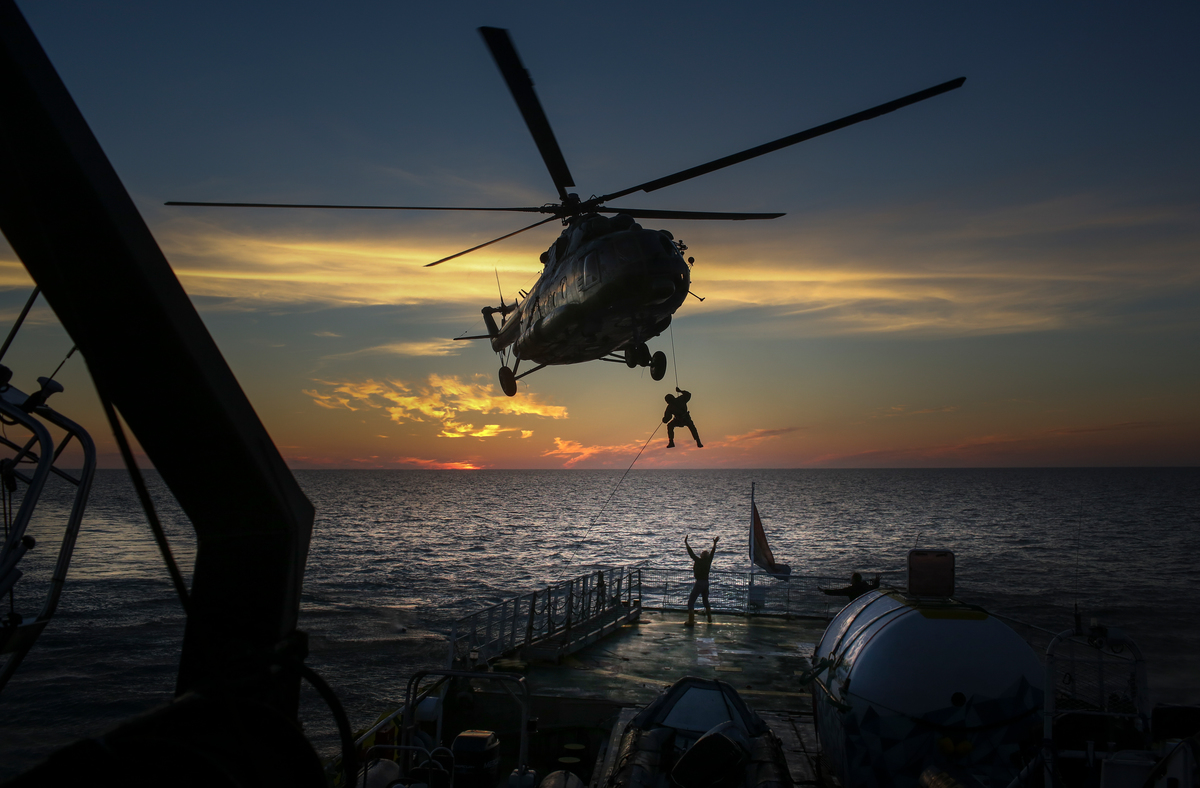 Armed Russian security services abseil from a helicopter onto the deck of the Arctic Sunrise (19 September, 2013). © Denis Sinyakov / Greenpeace