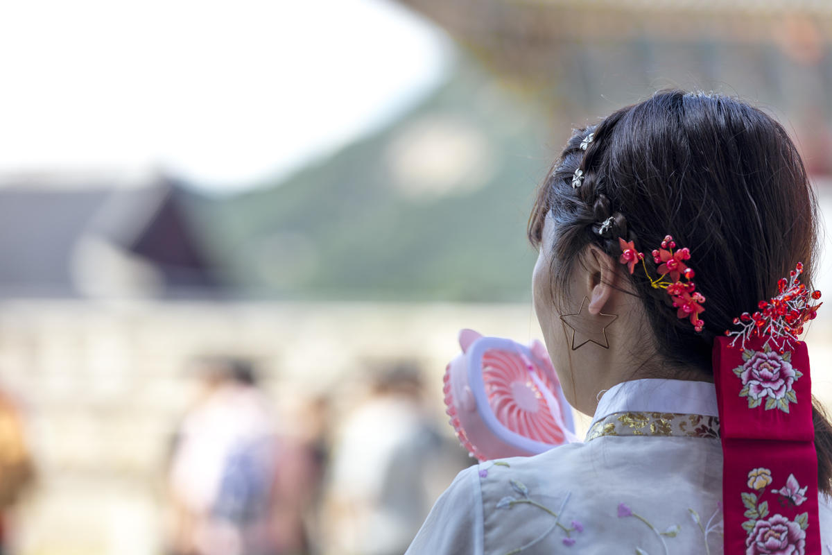 A tourist in Gyongbok Palace cools down from the heat using a toy fan. © Soojung Do / Greenpeace
