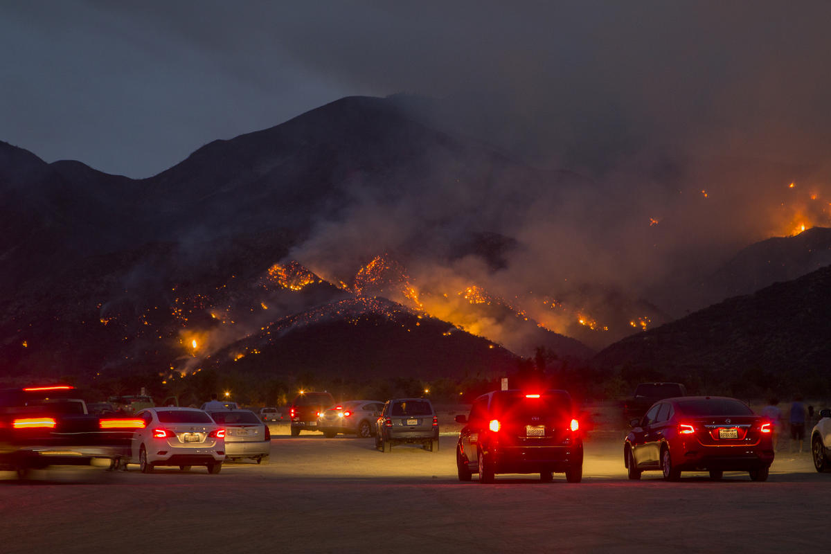 People watch flames as night falls during the Holy Fire near Corona, California. © David McNew / Greenpeace