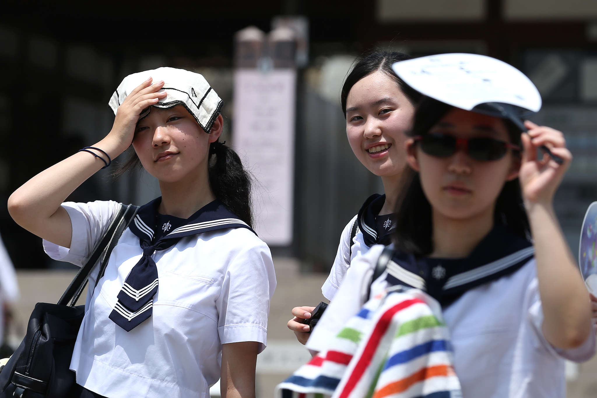 Japanese high school students use a handkerchief to cover their heads from sunlight as city temperature reach 36 degree celsius in Himeji, Japan. A natural disaster has been declared as thousands of people have been taken to hospital with heat stroke as the death toll continues to rise in Japan following the record-breaking heat wave. Photo: Buddhika Weerasinghe/Getty Images