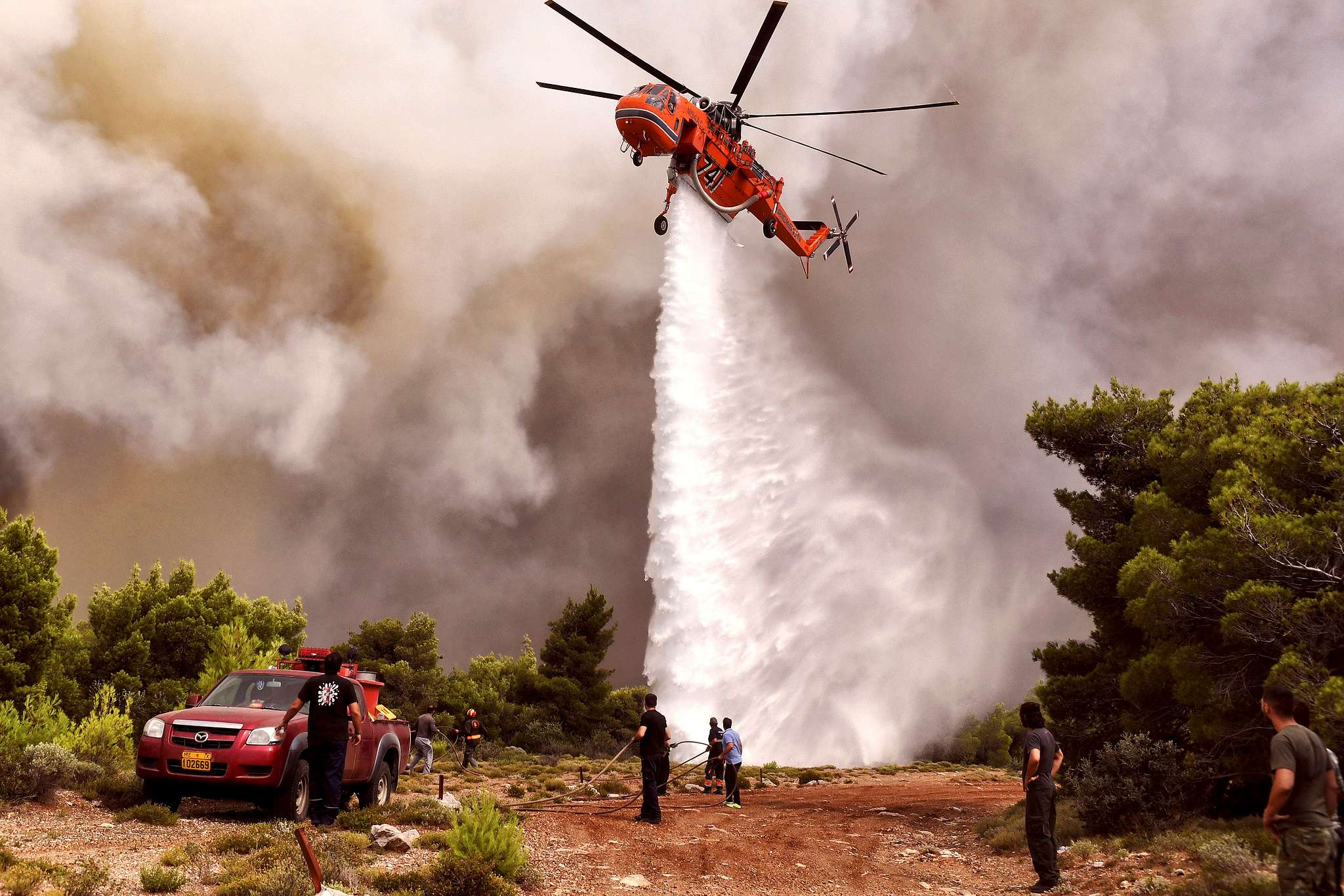 A firefighting helicopter drops water to extinguish flames during a wildfire at the village of Kineta, near Athens. Photo: VALERIE GACHE/AFP/Getty Images