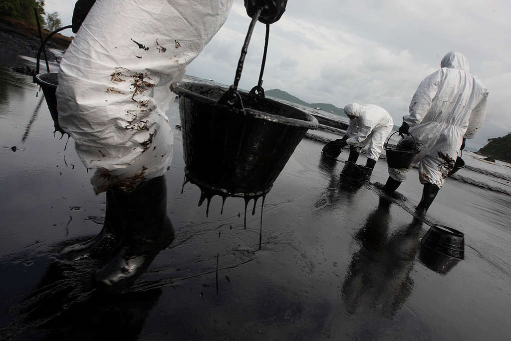 Rescue workers and local volunteers attempt to clean up the oil spill at Ao Phrao beach in Ko Samet, Rayong Province. (2013). © Roengrit Kongmuang / Greenpeace