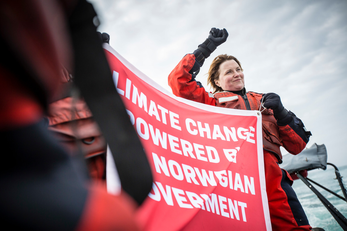 "Actress Lucy Lawless holds up a banner reading ""Climate change powered by the Norwegian government"". She joined other activists to oppose the Statoil Songa Enabler oil rig, 275 km North of the Norwegian coast, in the Arctic Barents sea © Will Rose / Greenpeace"