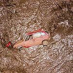 Car getting dragged away by the mud, © Fernanda Ligabue / Greenpeace