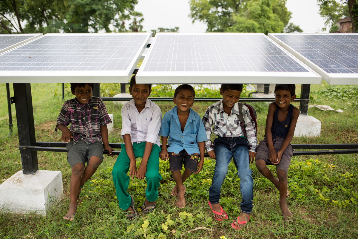 Children sit under solar panels in Dharnai village, India. © Vivek M. / Greenpeace