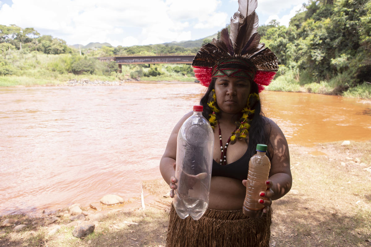 Werymerry Hã-hã-hãe with samples of water before and after the mud reached the Paraopeba River. © Nilmar Lage