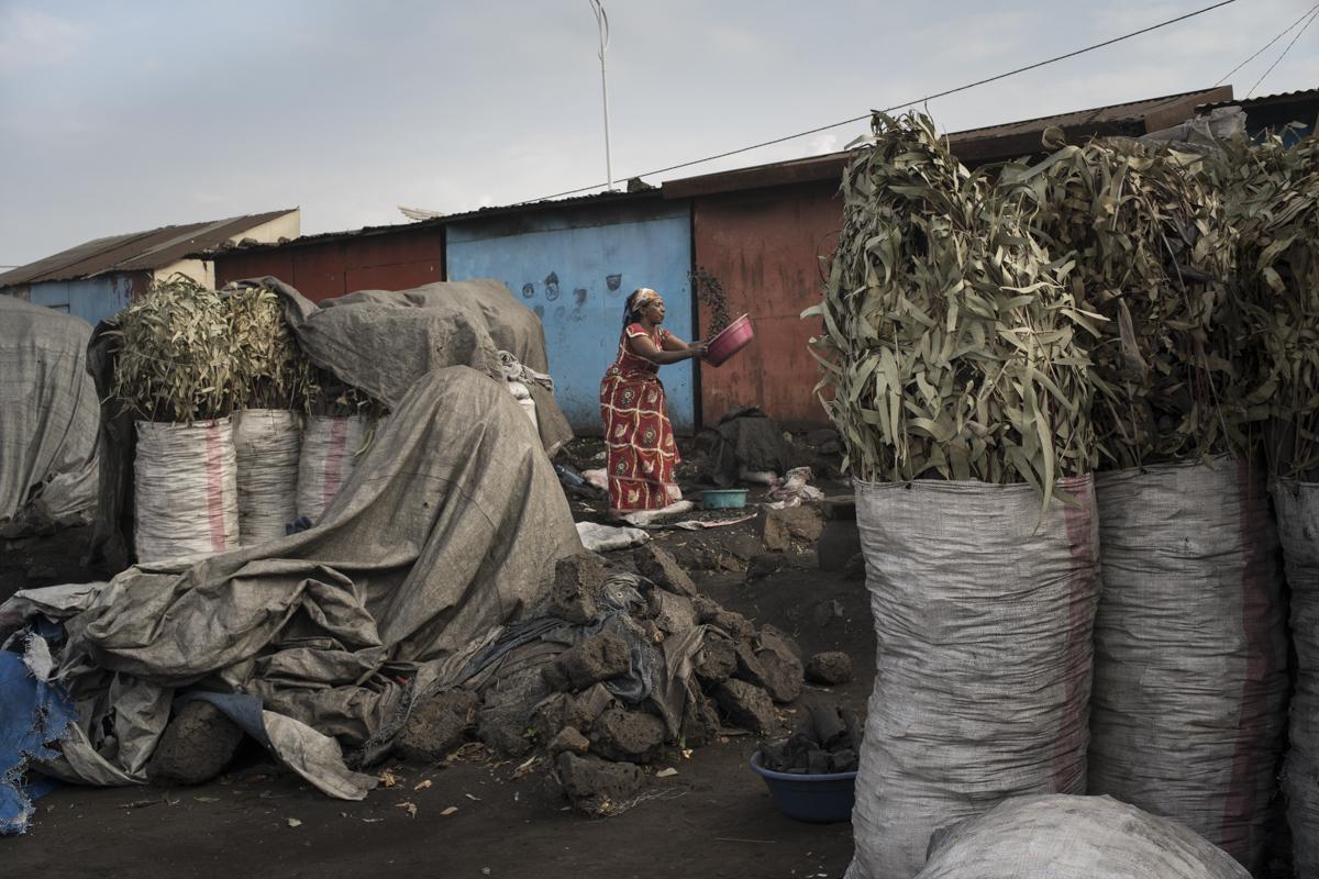 A woman sells charcoal in the market in Gysenyi, Rwanda. © Diana Zeyneb Alhindawi