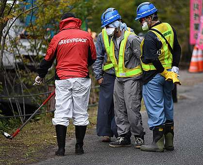Workers and Greenpeace radiation specialist, Ray Lei, Obori, inside the Namie exclusion zone, Fukushima prefecture. © Shaun Burnie