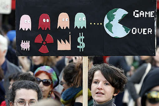 "PARIS, FRANCE - MARCH 16: A protester holds a sign reading ""Game over"" as he takes part in the ""March of The Century"" (La Marche du Siecle) to demand answers to climate change on March 16, 2019 in Paris, France. Several thousand people demonstrated in Paris to denounce the government's inaction on climate. Chesnot/Getty Images"
