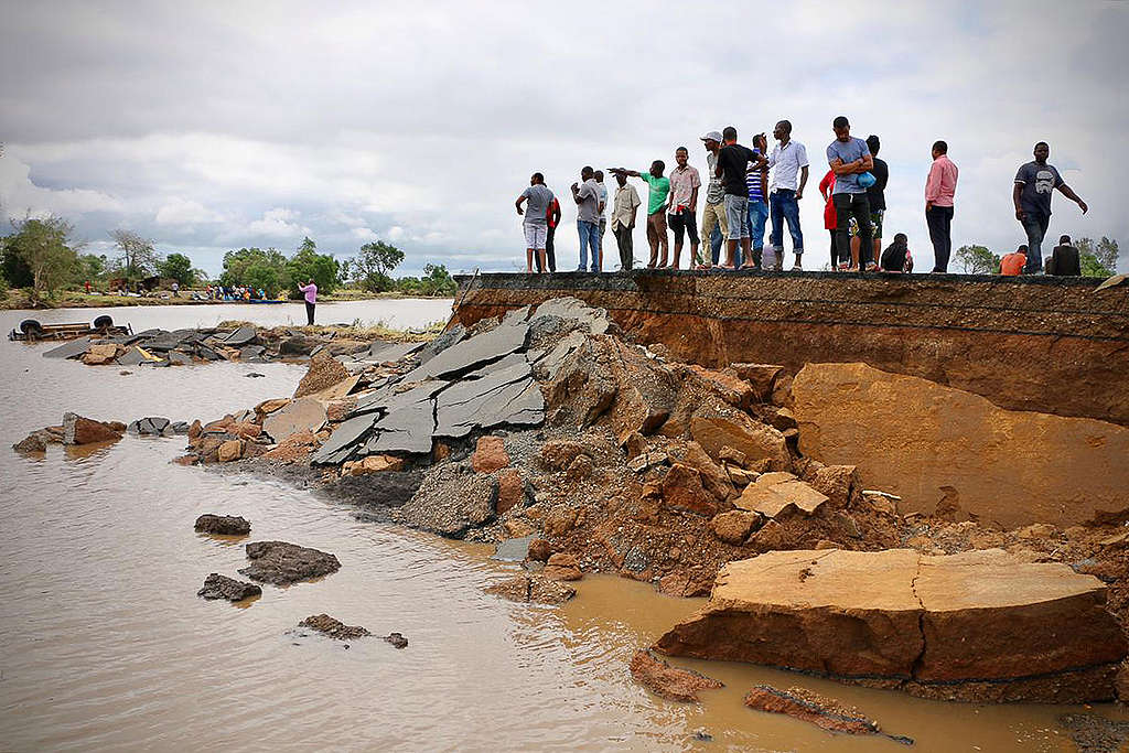 Locals stand beside a damaged section of the road between Beira and Chimoio © ADRIEN BARBIER/AFP/Getty Images