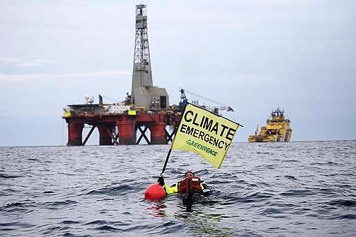 Greenpeace swimmer in front of BP rig. © Greenpeace