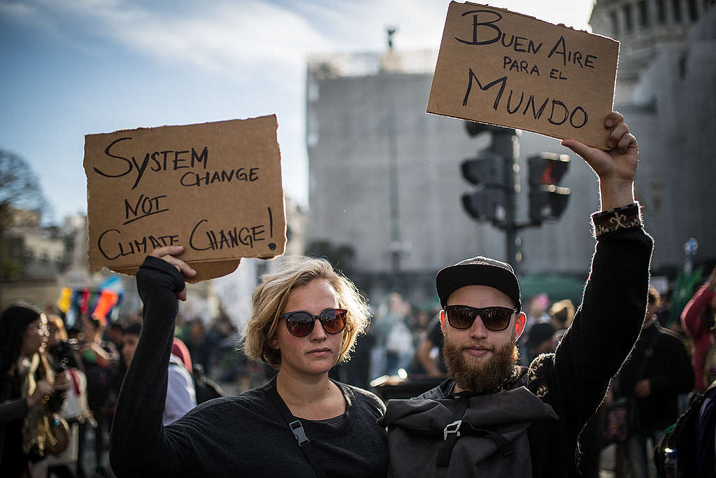 ©Nicolás Villalobos/Greenpeace Activists holding up signs demanding clean air and system change at a climate march in Buenos Aires, Argentina