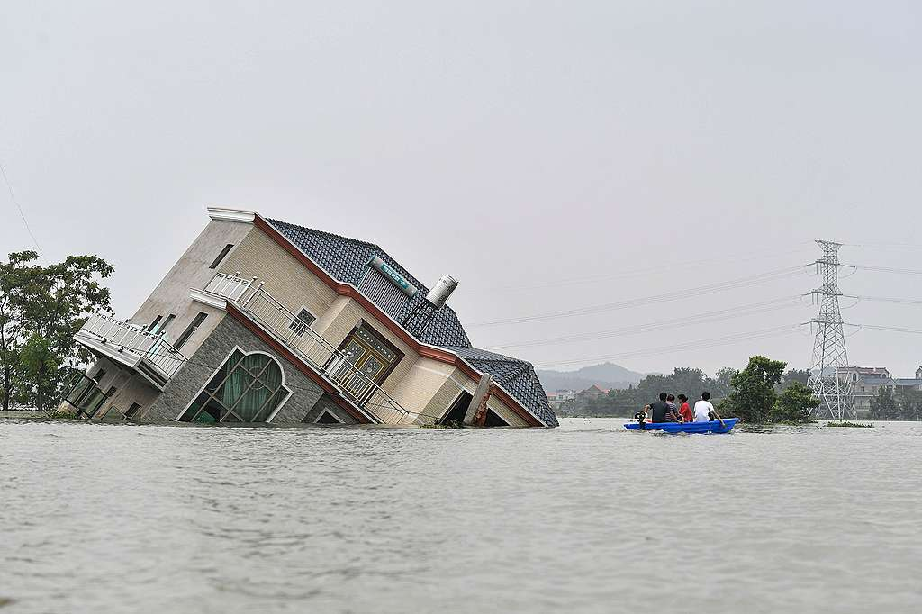 Residents riding a boat past a damaged and flood-affected house near the Poyang Lake due to torrential rains in Poyang county, Shangrao city in China's central Jiangxi province. © STR/AFP via Getty Images