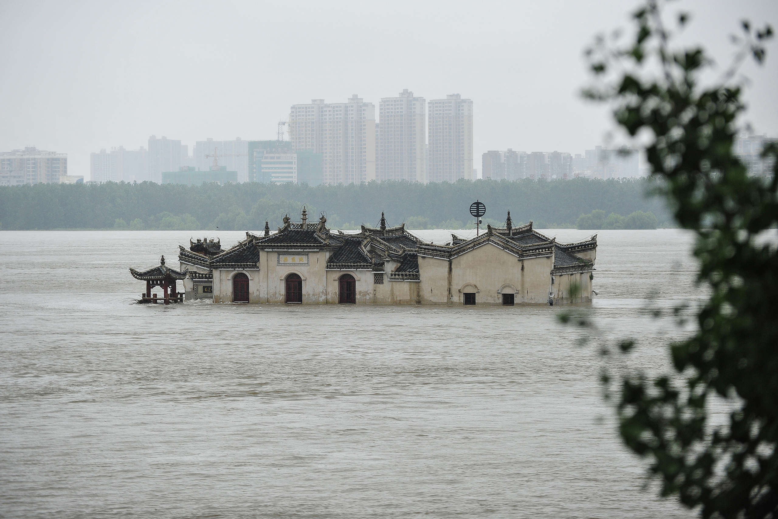 The Guanyinge temple, a 700-year old temple built on a rock, in the swollen Yangtze River in Wuhan in China's central Hubei province. - Heavy rains since June have left at least 141 people dead and missing, forced nearly 15 million people to be evacuated from their homes in July alone. © STR/AFP / Getty Images