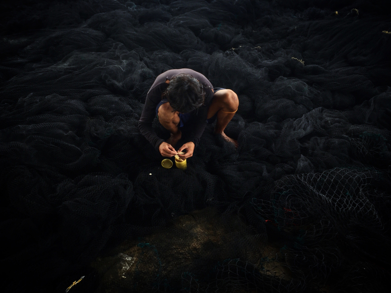 A fisherman repairs a Thai purse seine in Ranong, southern Thailand.
