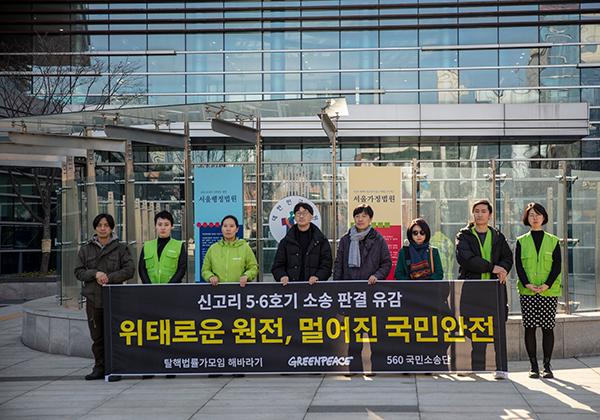 """서울행정법원 앞에서 그린피스 활동가들과 560 소송단이 신고리 5,6호기 건설 허가 취소소송 사정 판결에 유감을 표하며 """"위태로운 원전, 멀어진 국민안전""""이라고 쓰인 배너를 들고 있다."""