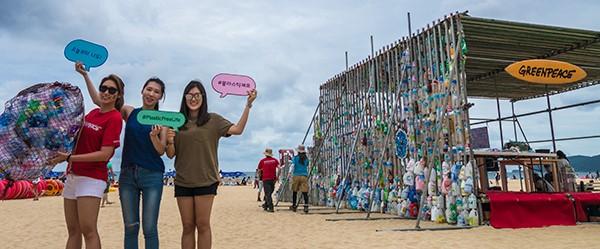 부산 해운대 해수욕장에 설치된 일회용 플라스틱 고래 조형물 앞에서 그린피스 캠페이너들이 일회용 플라스틱 더미와 '플라스틱제로' 팻말을 들어보이고 있다