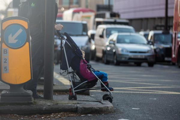 어린 아이가 유모차를 타고 길을 건너기 위해 신호를 기다리고 있다